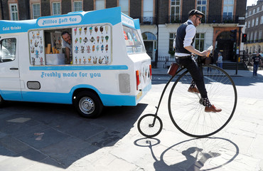 A participant in the Tweed Run cycle ride pulls away from an ice cream van in London
