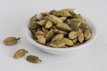 Green Cardamom pods in a white bowl
