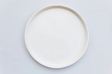 Top view of white empty plate on white tablecloth. Wall mural