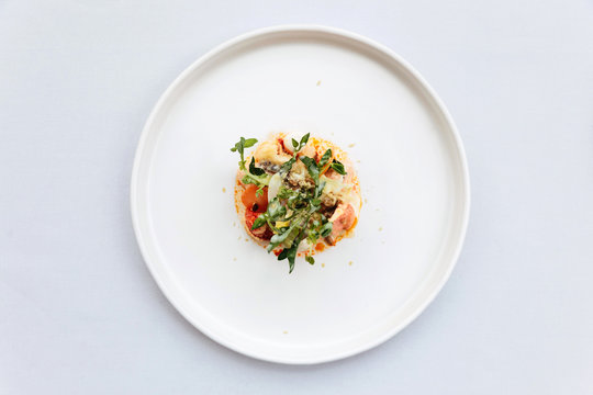 Modern French cuisine: Top view of lobster tail salad including lobster, asparagus and roasted sunflower seeds with white sauce served in white plate.