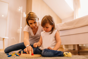 Young mother is playing with wooden toy with daughter on bedroom floor