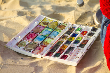 Colorful watercolor set placed on sandy beach
