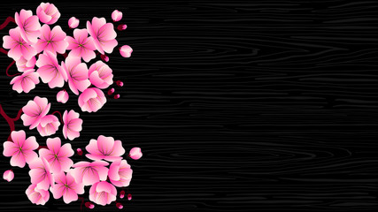 Cherry blossom branch with pink flowers on a black wood texture.