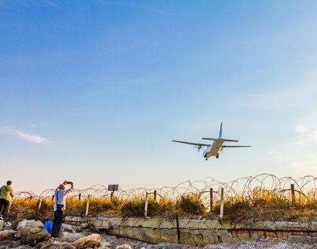 People photographing a turboprop airplane landing at Larnaca International Airport
