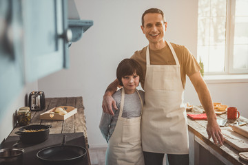 Portrait of father and kid making pastry in kitchen. They standing in embrace and looking at camera with satisfaction