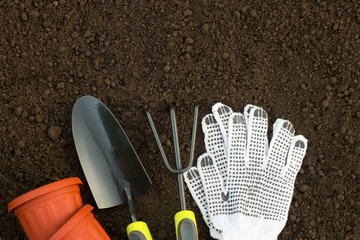 Gardening tools, gloves and flower pots on the ground in the garden