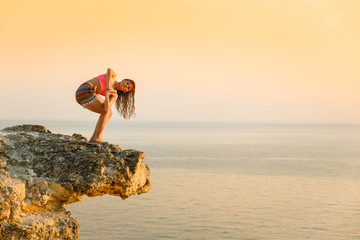 Meditation on the beach. A woman is standing on a cliff above the ocean and doing yoga. Femininity. Force. Soft shades at sunset. Beautiful scenery. You're on top of the world.