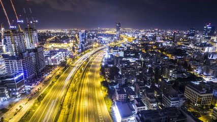 Night aerial view of tel aviv skyline with urban skyscrapers and Long exposure car tail lights at ayalon highway, Israel