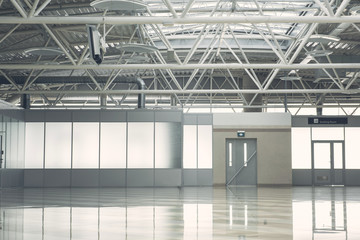 Wide light hall with grey door and concrete floor. Warehouse concept