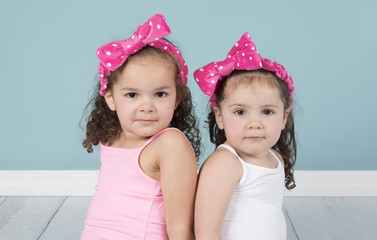 Curly haired little girls in pink polka dot headbands looking at camera with cute expressions