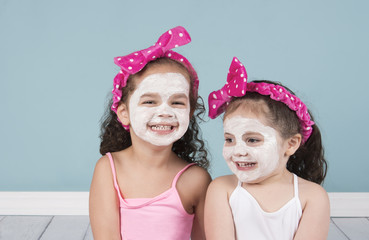 Laughing little girls in beauty face masks and polka dot headbands