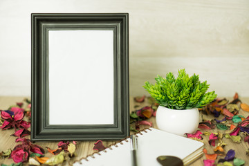 Photo Frame on Wood Table with Notebook, Dry Flower Petals and Potted Plant.