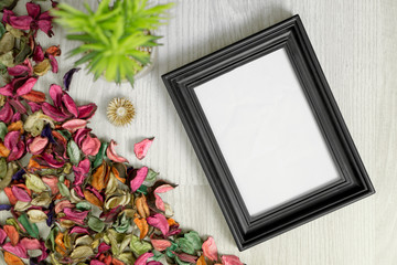 Photo frame on white wood background with potted plant and dry flower petals. Rustic nostalgia.