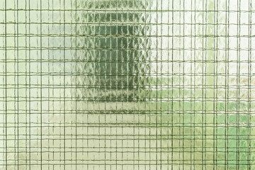 glass with reinforcing mesh, silhouette of windows and doors behind glass
