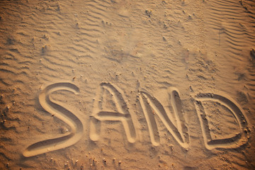 the word sand is written in the sand