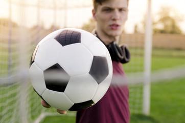 Closeup Teen holding soccer ball in the goal, selective focus on ball