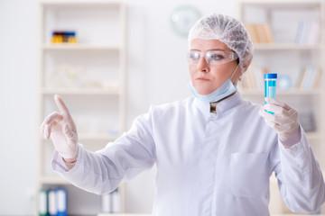 Woman chemist pressing virtual button in lab
