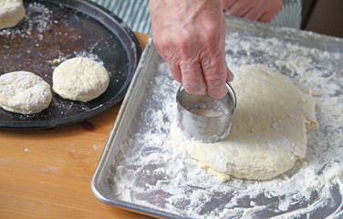 Using a metal cutter, an older man cuts out biscuits from dough