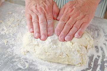 Overhead view of man pressing dough to a uniform thickness