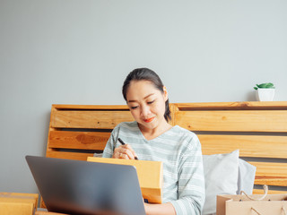Woman ready to ship the products of her online store to the customer. Concept of work at home online business.
