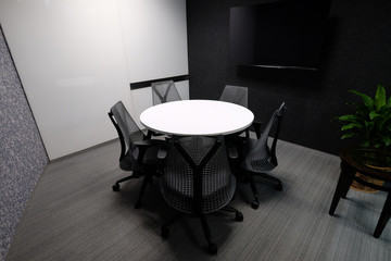 Small meeting room for five people with whiteboard and television accessory