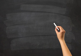 Female hand holding white chalk in front of a blank blackboard