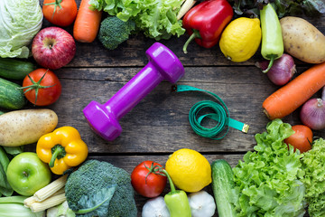 Top view of Dumbbell with fruits and vegetables on the old wood table with copy space