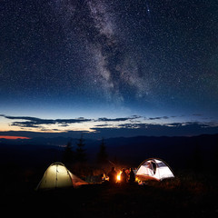 Family backpackers mother, father, two guys resting at night camping in mountains, beside campfire and two illuminated tents, under incredible beautiful view of evening sky full of stars and Milky way