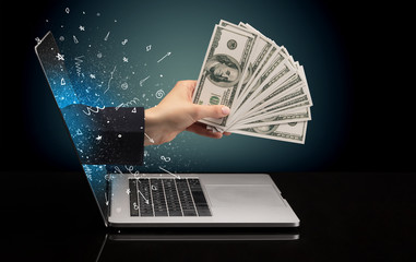 Hand with money coming out of a laptop with sparkling effects