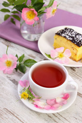 Cup of hot tea with cheesecake and wild rose flower on old board