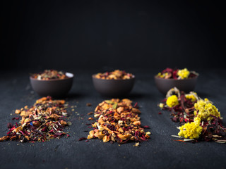 Set of different herbal and fruit dry teas in clay bowls, dark moody, stone,concrete background.