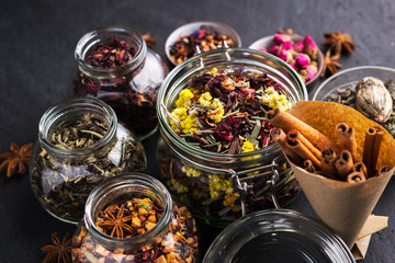 A set of various herbal and fruit teas in glass jars on a dark background. Medicinal herbs. A natural, eco product.