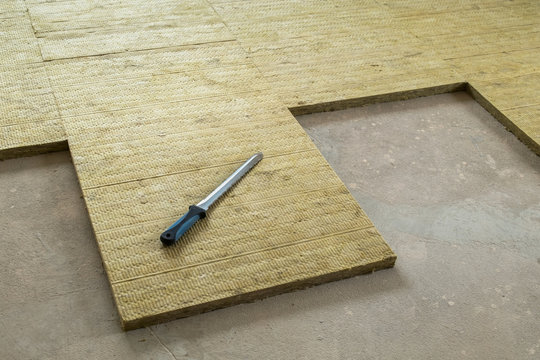 Thermal and sound protection in the interior of the apartment. Mounting knife and insulating mats made of stone wool on the floor of the apartment.