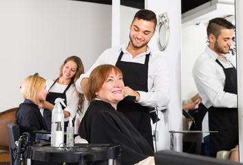 Barber cuts hair mature person