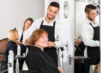 Woman cuts hair at the hair salon with barber