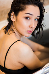 Closeup portrait of a young woman sits in the bathtube