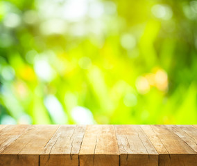 Empty of wood table top on blur of fresh green abstract from garden backgrounds