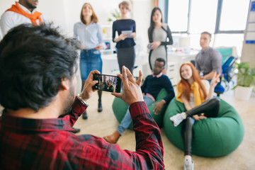 close up back view shot of young male shooting the mixed race participants of training with blurred background in the office with panorama window