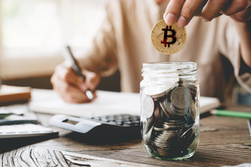 Businessman putting bitcoin into piggy bank and using calculator to analysis business investment with many document graph data, CryptoCurrency Financial Concept.bit