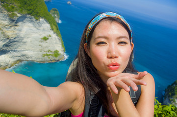 young beautiful and happy Asian Korean tourist woman taking self
