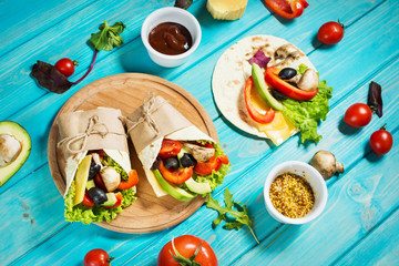Healthy vegan lunch snack. Tortilla wraps with mushrooms, fresh vegetables and Ingredients on blue wooden background