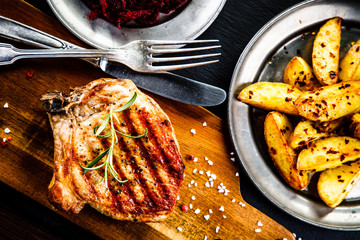 Grilled steak, French fries and vegetables on wooden background