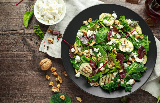Grilled Zucchini salad with feta cheese, walnut nuts and glass of red wine in a black plate on wooden table