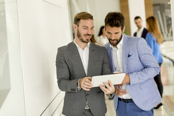 Two young businessmen with digital tablet in office