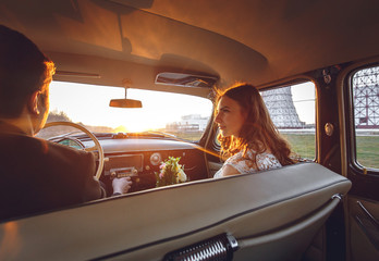 Young wedding couple sitting smiling inside retro car and looking at each other. just married embrace is hugging inside car. bride hugging groom who is driving the car. Wedding with retro car.