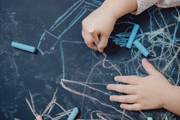 Close-up of child hand draws on chalkboard, top view, concept development of art for children
