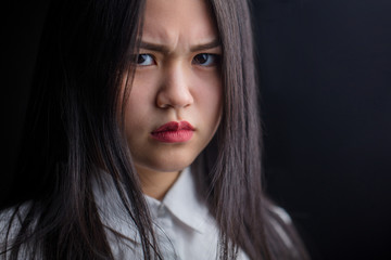Close up of displeased asian woman with frowny face and resentful look against black background