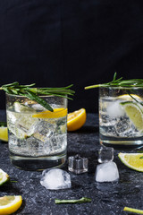In de dag Cocktail Alcoholic drink gin tonic cocktail with lemon, rosemary and ice on stone table