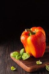 Red and yellow bell pepper on a cutting board with basil leaves on wooden background. Copy space. Fresh bell pepper wased for cooking.
