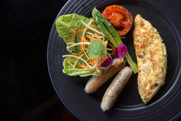 Western breakfast omelet with sausages, tomatoes, pepper and greenery